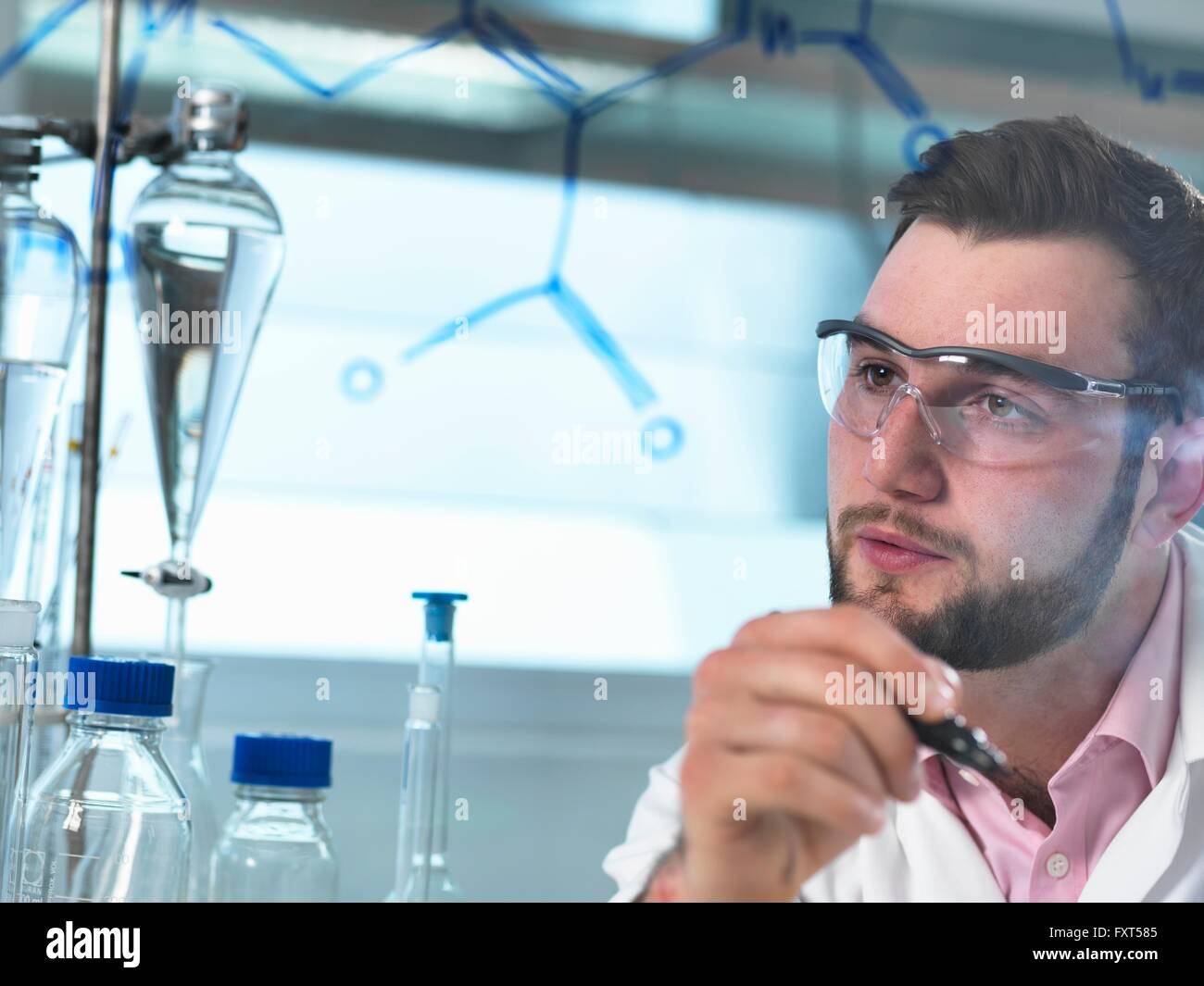 Young male scientist looking at antibiotic chemical formula in pharmaceutical research lab - Stock Image
