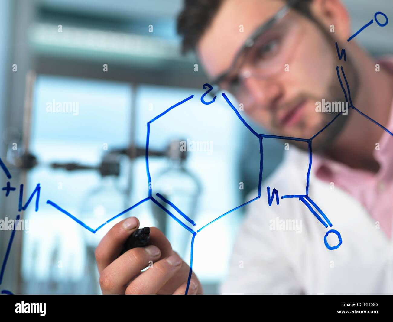 Young male scientist illustrating antibiotic chemical formula in pharmaceutical research lab - Stock Image