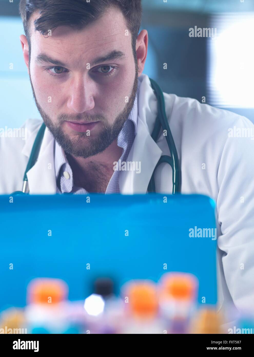 Doctor reading patient medical test results on laptop, samples in foreground - Stock Image