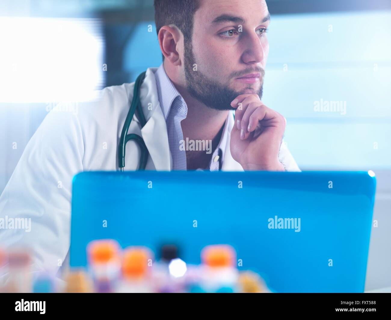Doctor thinking about patient medical test results, samples in foreground - Stock Image