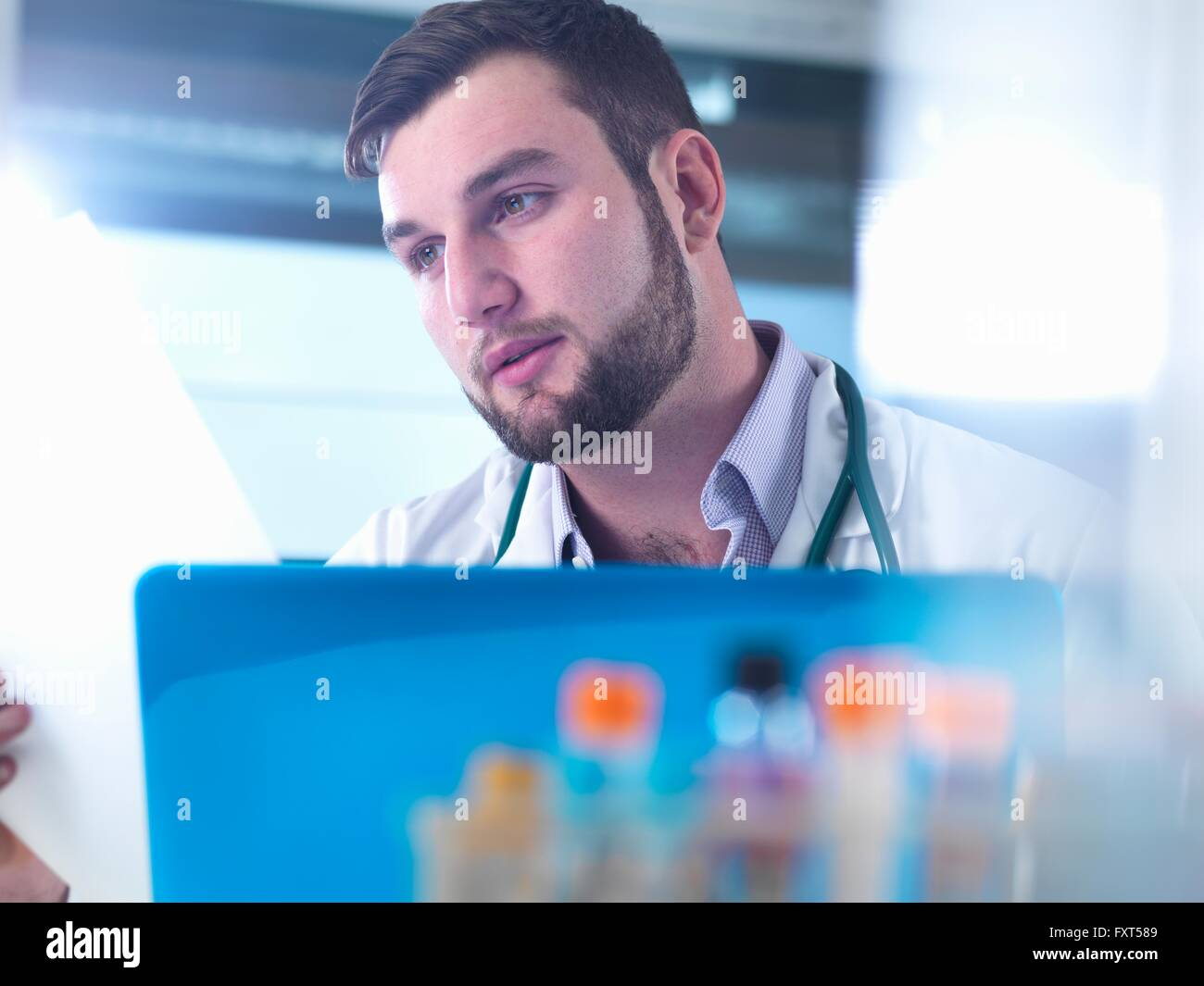 Doctor reading patient medical test results, samples in foreground - Stock Image