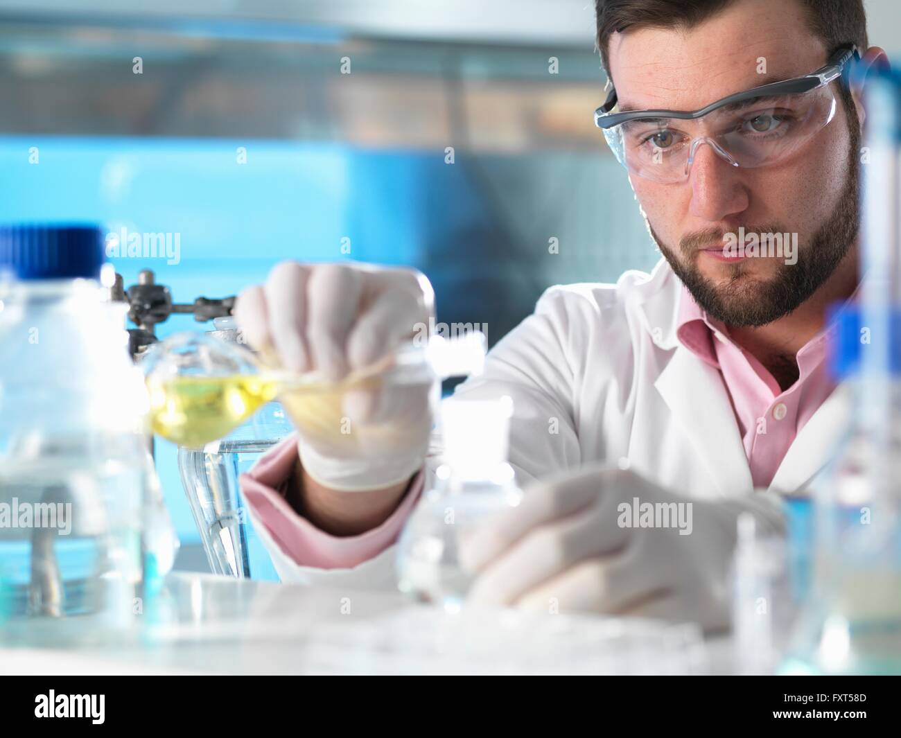 Scientist experimenting with chemical formula in laboratory - Stock Image