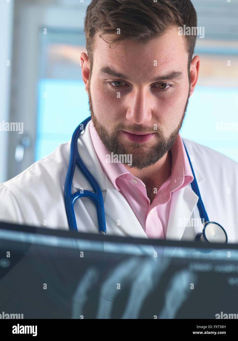 Young male junior doctor examining x-ray of fractured hand in hospital - Stock Image