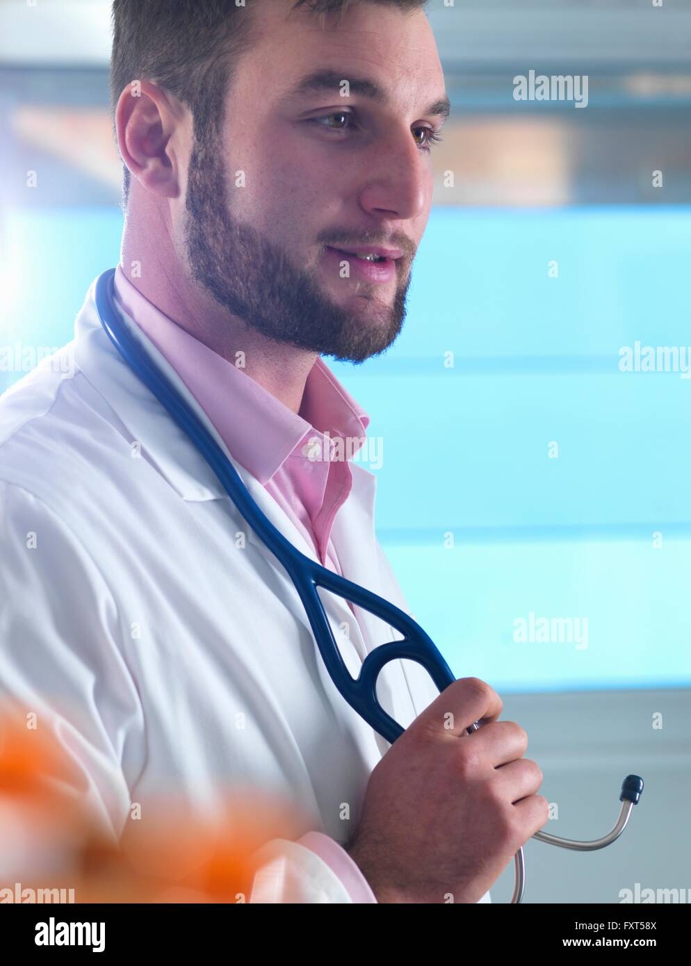 Portrait of young male junior doctor in clinic - Stock Image