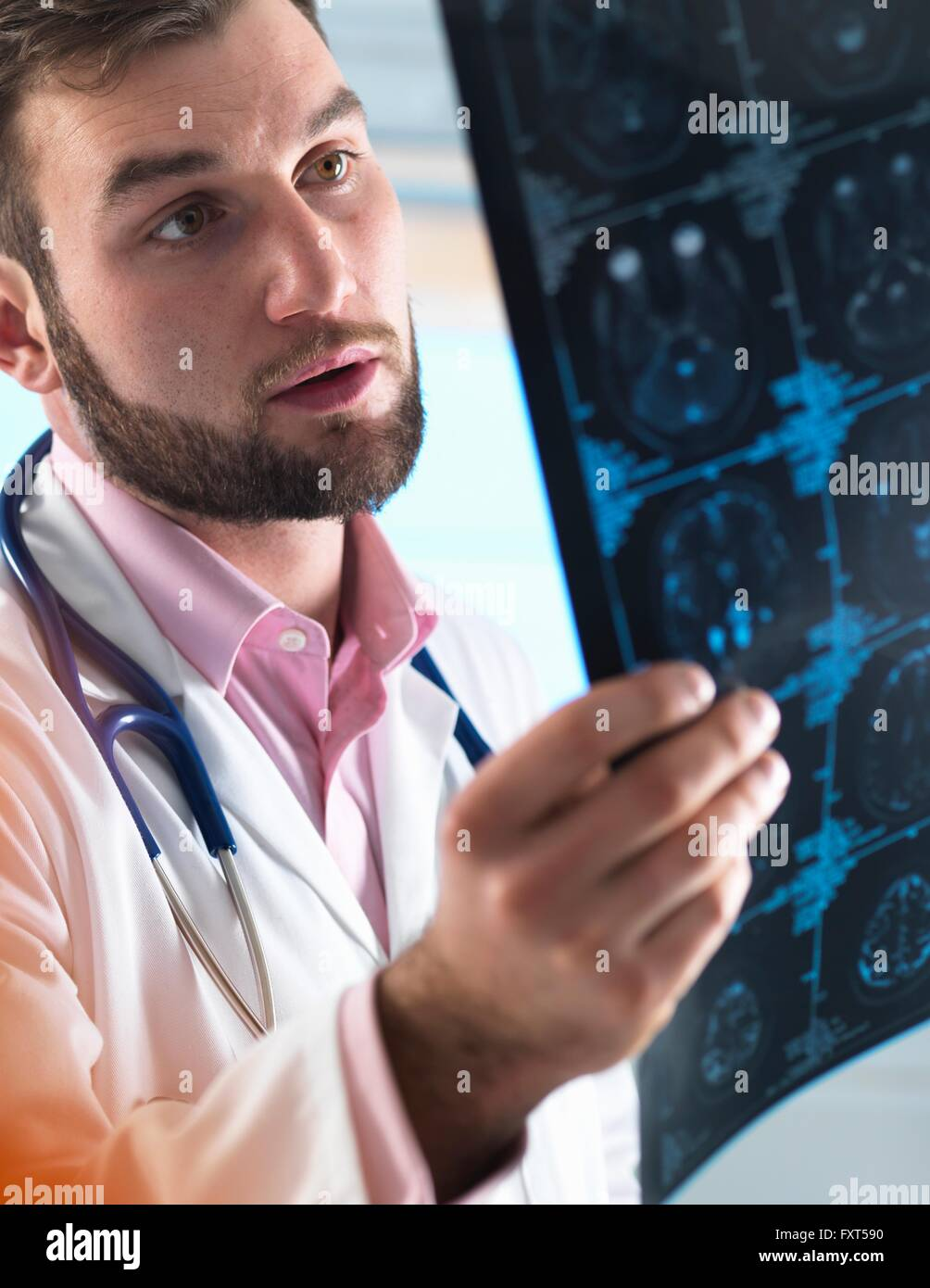 Young male junior doctor examining a brain scan in hospital - Stock Image