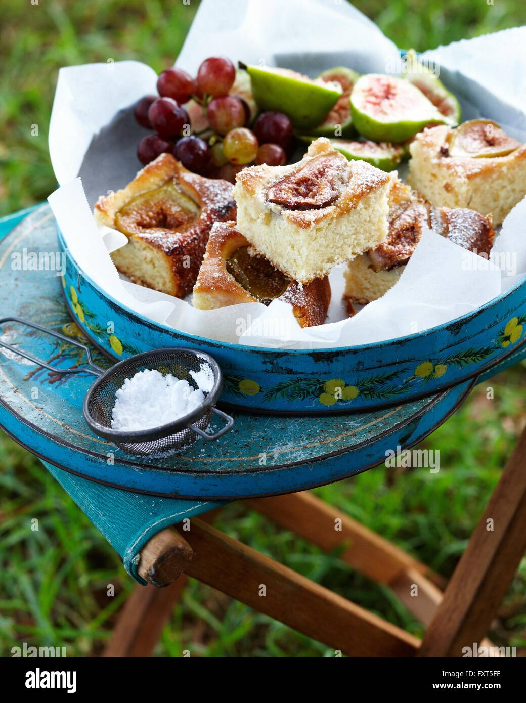 Coconut cake with figs and grapes in cake tin - Stock Image