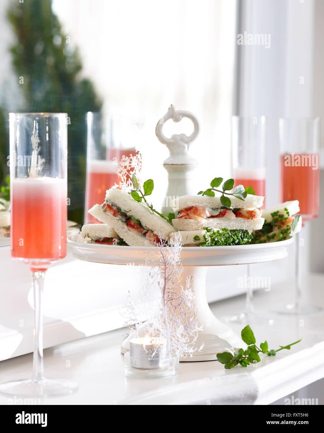 Champagne flutes of pink champagne and crayfish sandwiches on cake stand - Stock Image