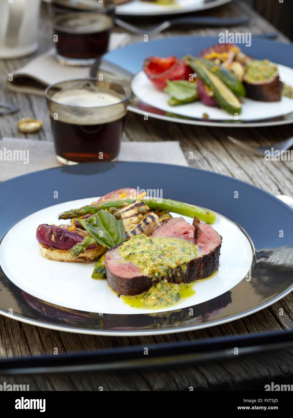 Close up of chimichurri Beef with barbecued salad outdoors on wooden garden table Stock Photo