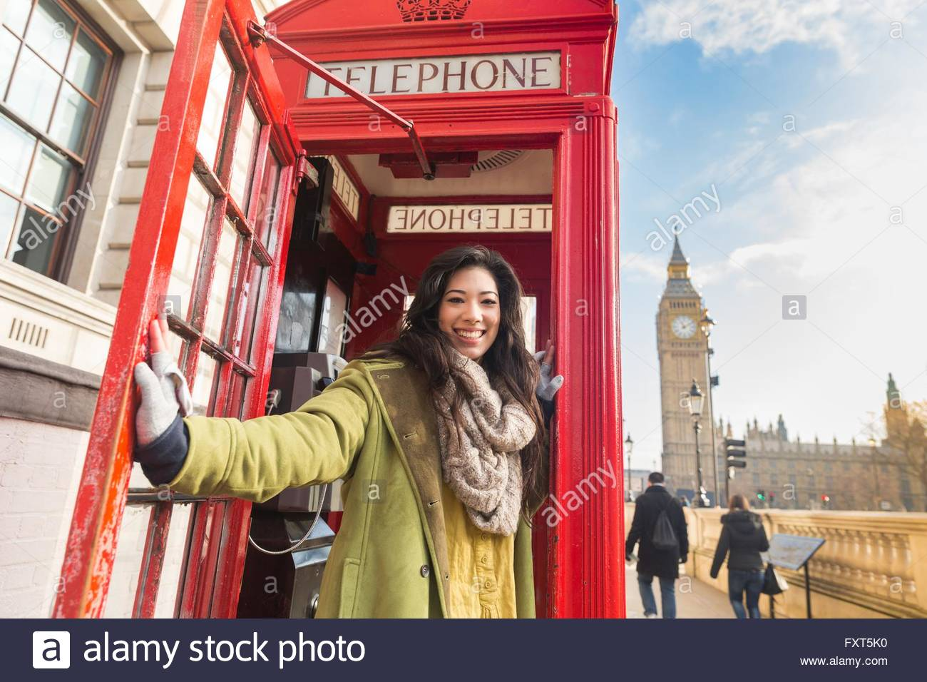 Young woman in traditional red phone booth holding door open looking at camera smiling London UK  sc 1 st  Alamy & Young woman in traditional red phone booth holding door open looking ...