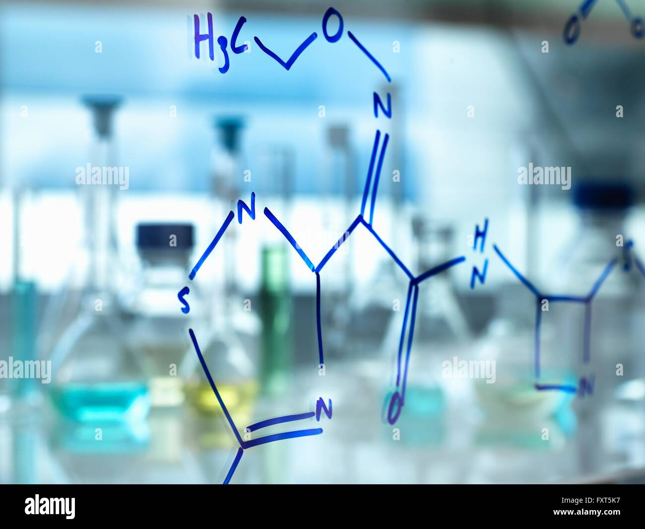 Chemical formula of antibiotic drug written on glass in laboratory - Stock Image