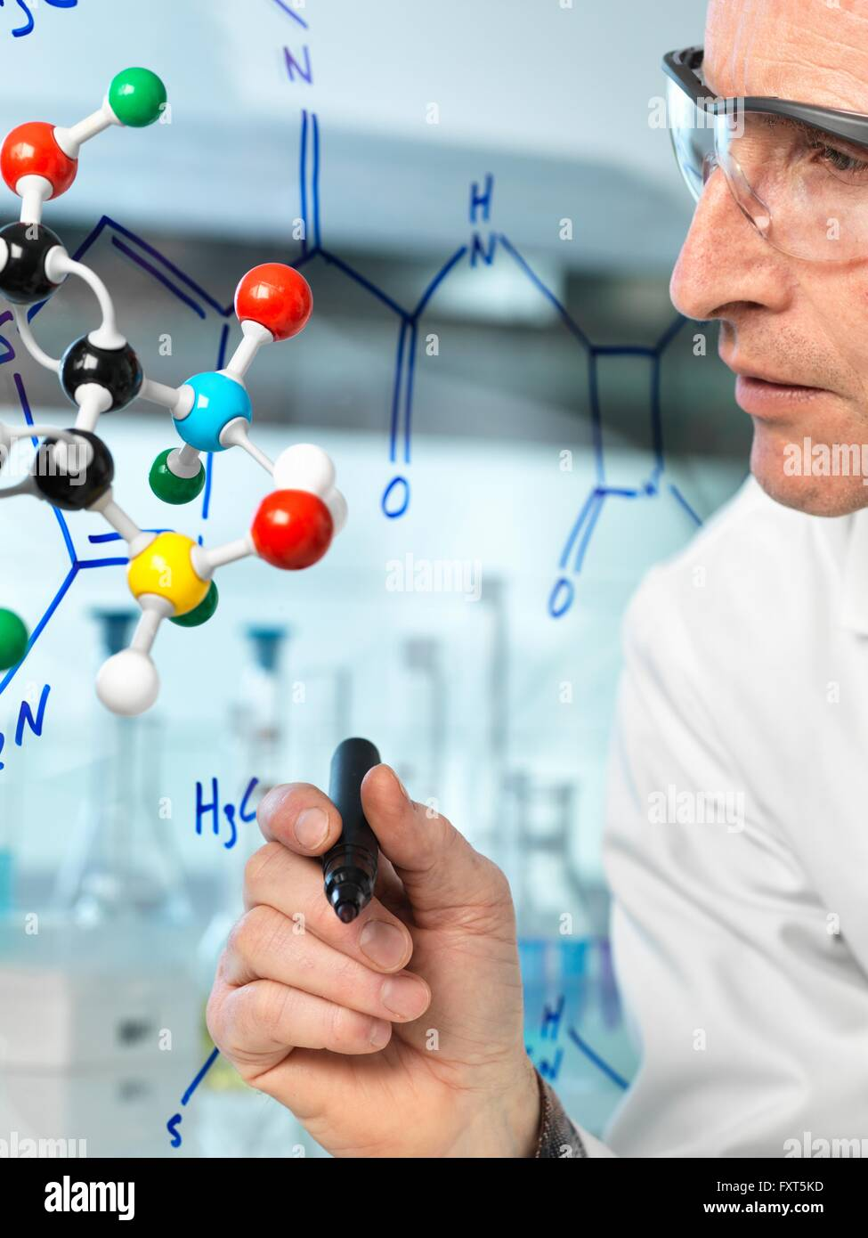 Scientist with ball and stick molecular model writing formula of new drug on glass - Stock Image