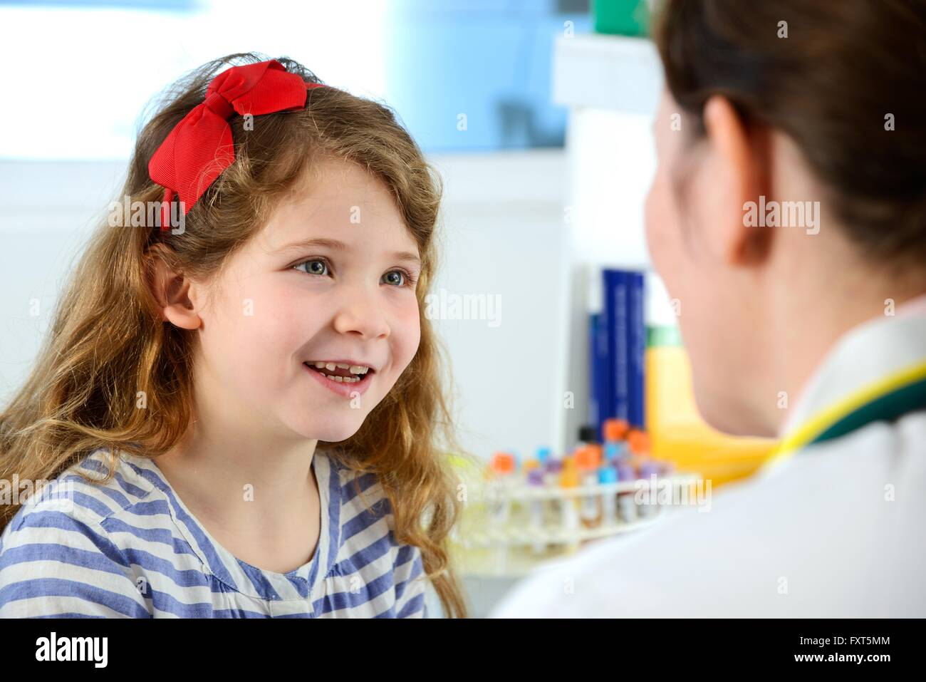 View over shoulder of girl consulting with doctor in clinic, smiling - Stock Image