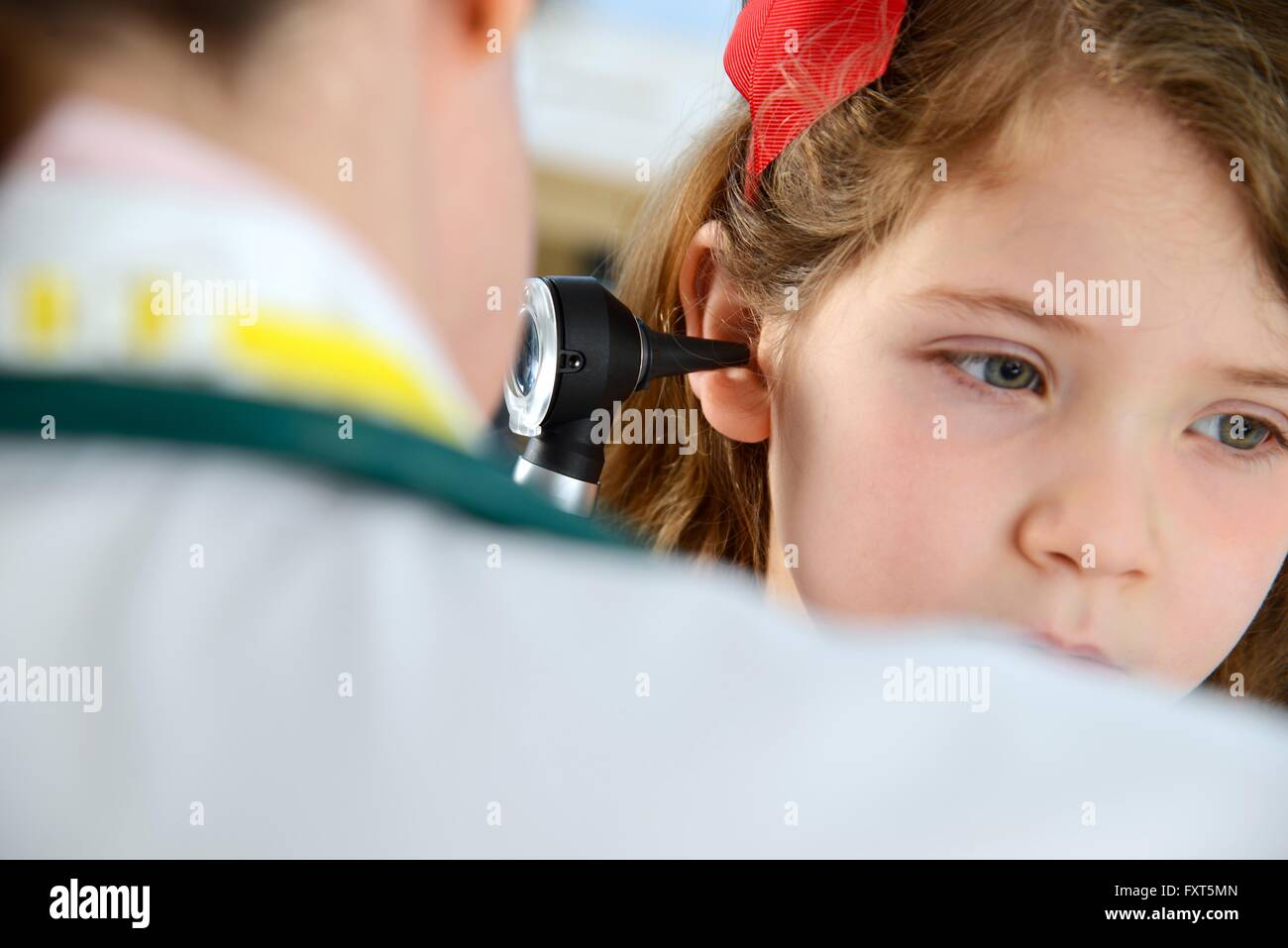 View over shoulder of doctor conducting otoscopy examination on girl - Stock Image