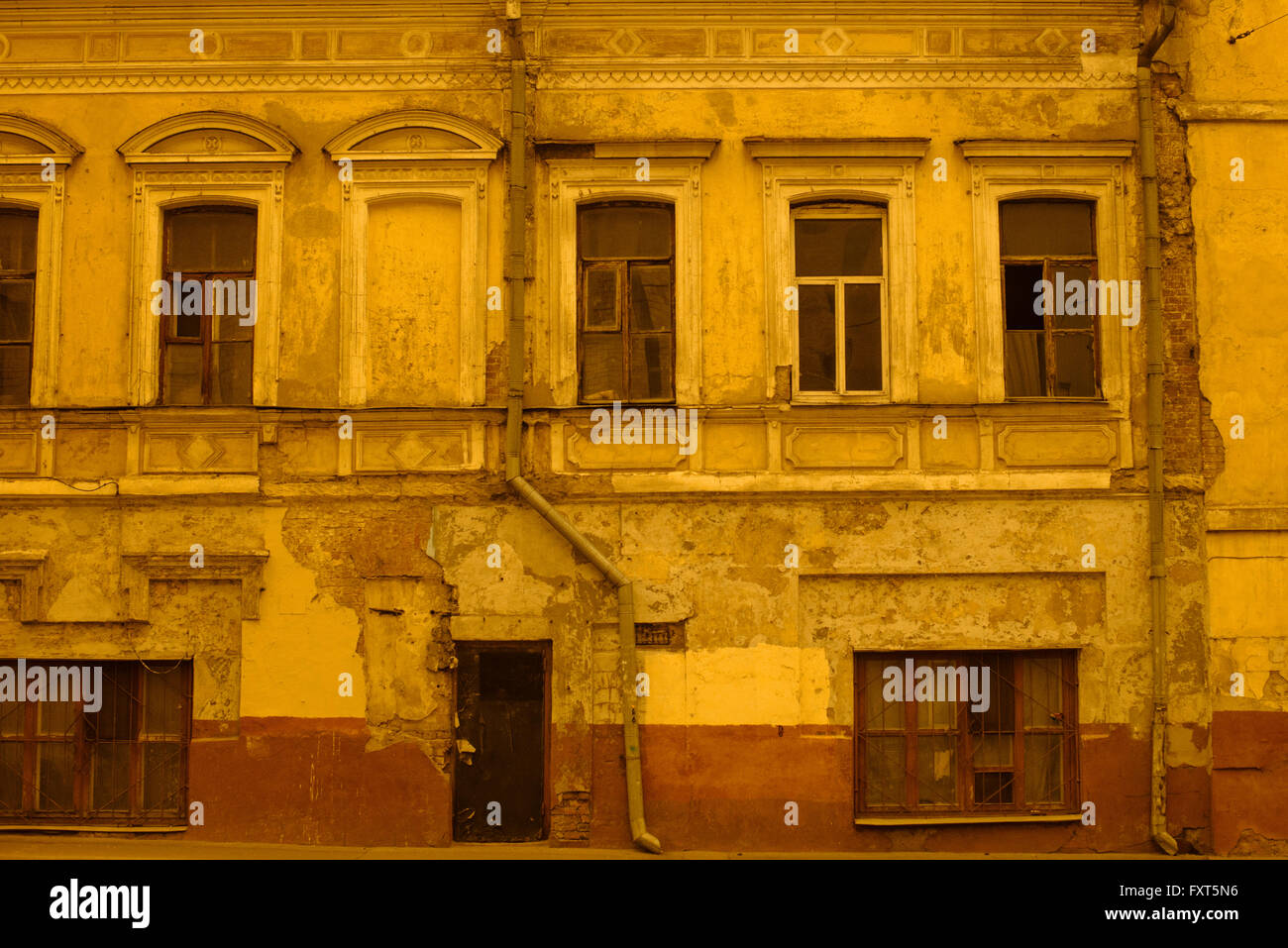Old abandoned house in Moscow city center (Savinskiy pass). Image is captured with orange filter to minimize colours - Stock Image
