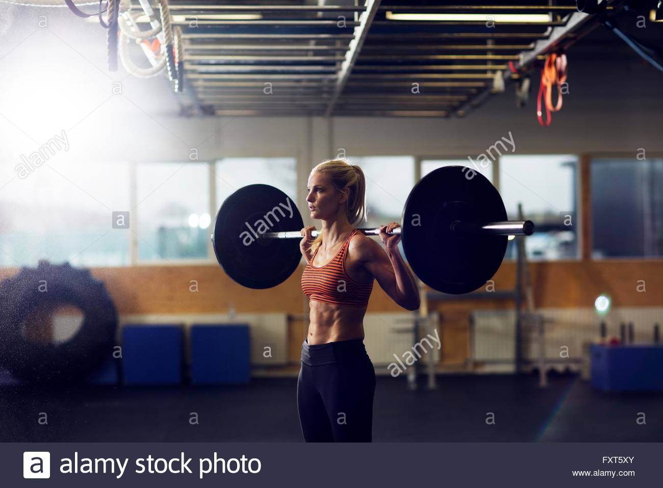 Woman lifting barbell on shoulders in gym - Stock Image