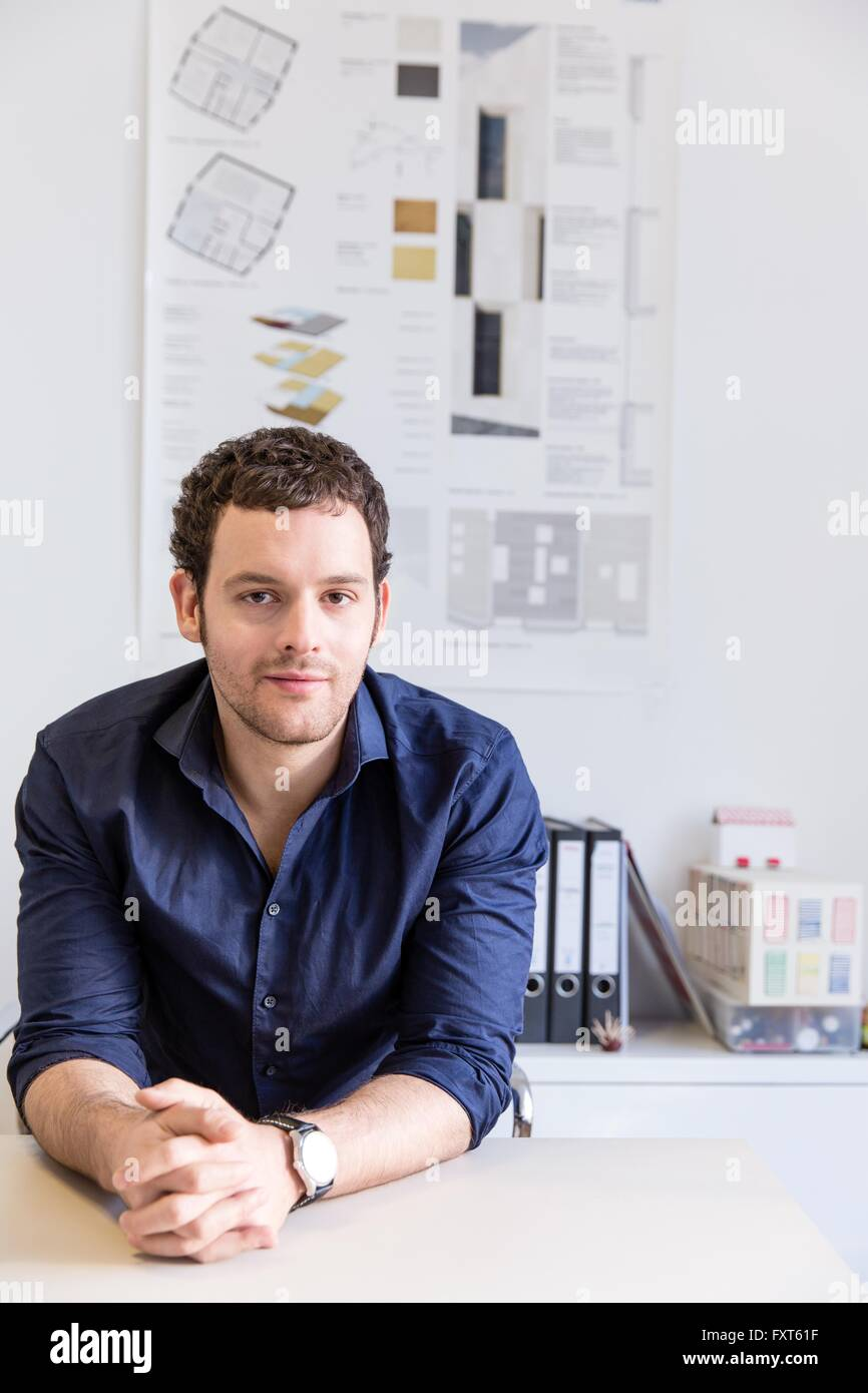 Mid adult man at desk in office in front of blueprint looking at camera - Stock Image
