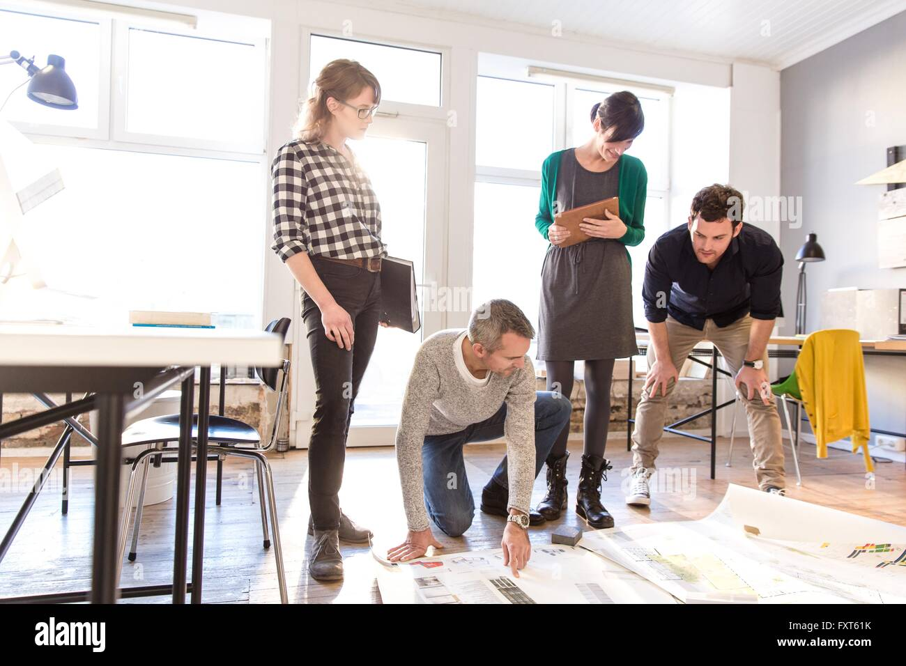 Architects discussing blueprint on office floor - Stock Image