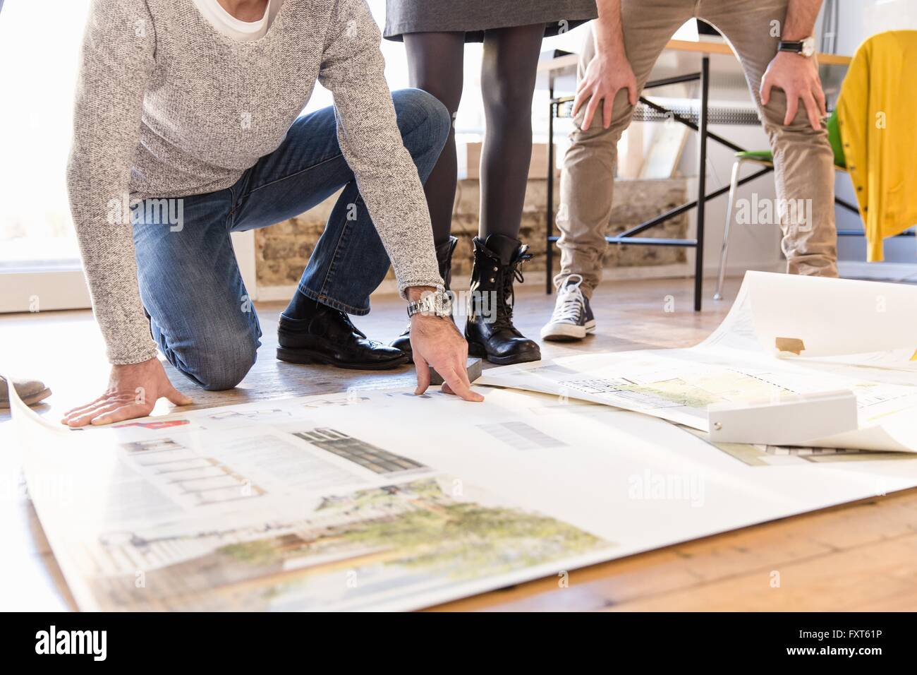 Low section of architects discussing blueprint on office floor - Stock Image