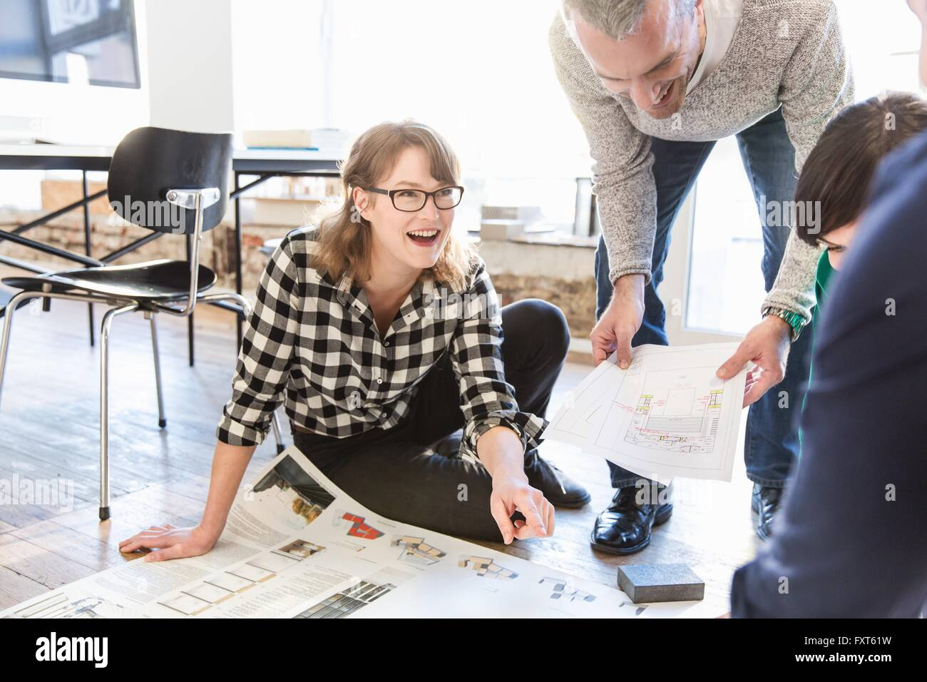 Architects on office floor discussing blueprint smiling - Stock Image