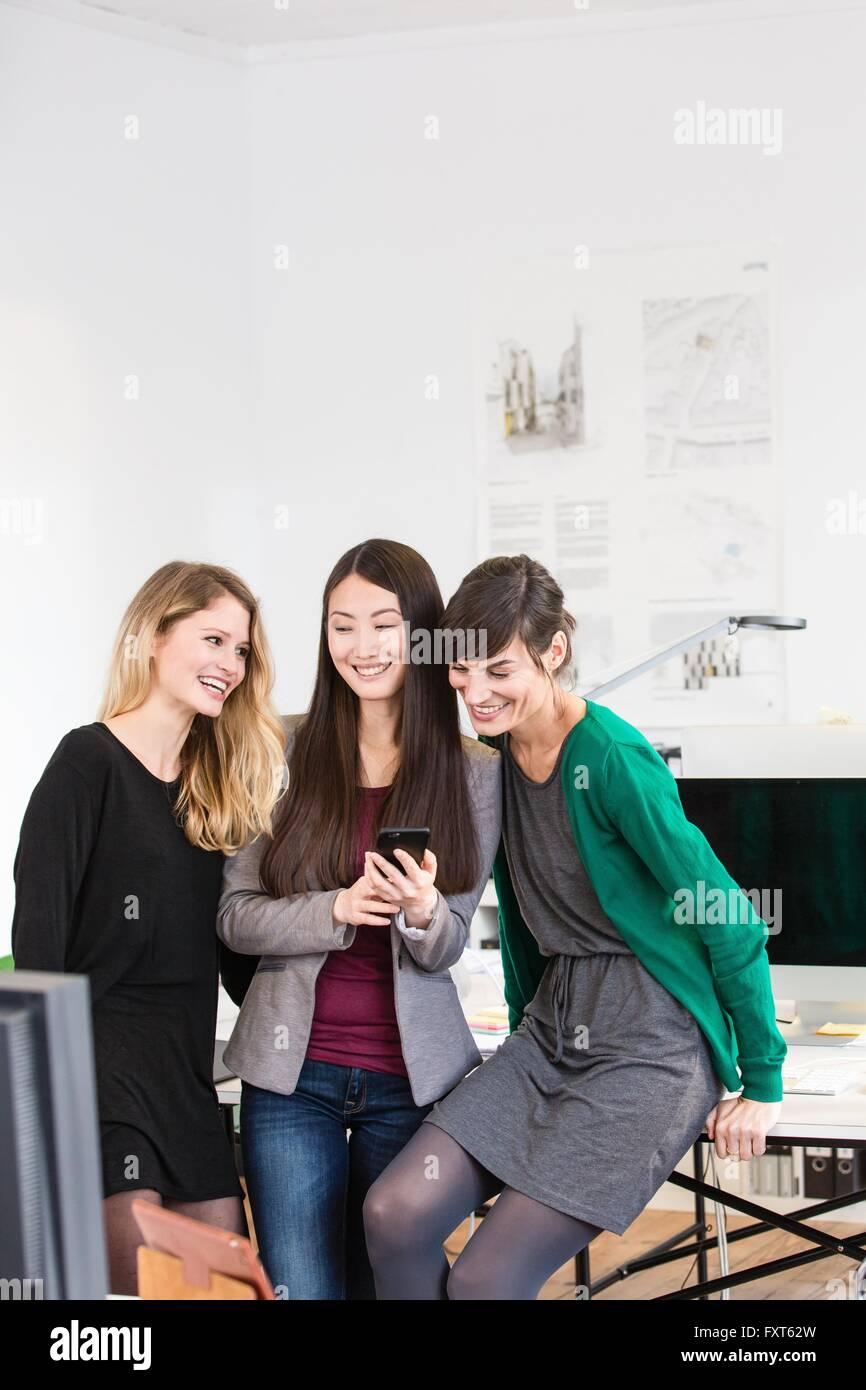 Colleagues in office looking down at smartphones smiling - Stock Image