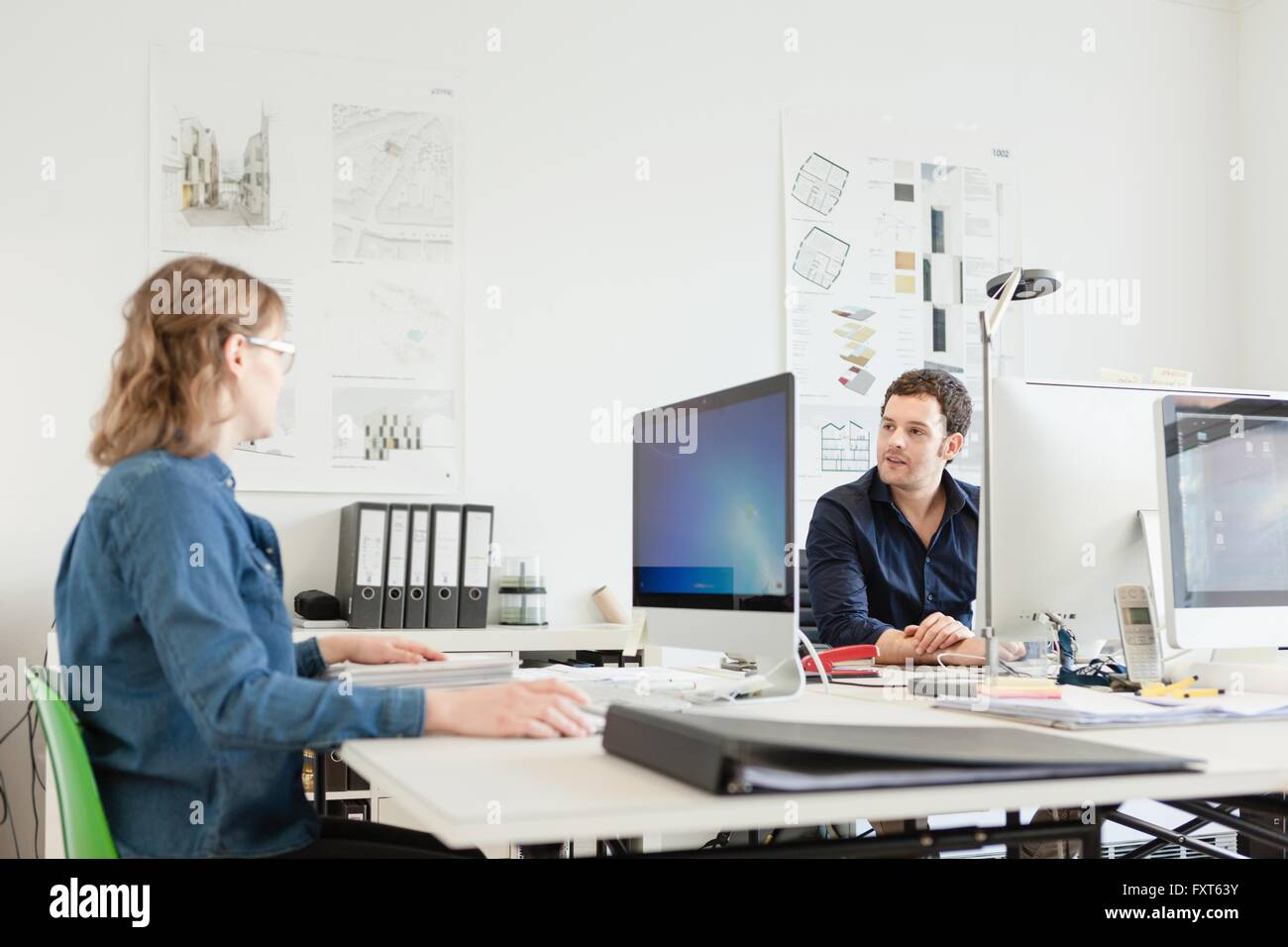 Colleagues sitting at desk in office using computers talking - Stock Image