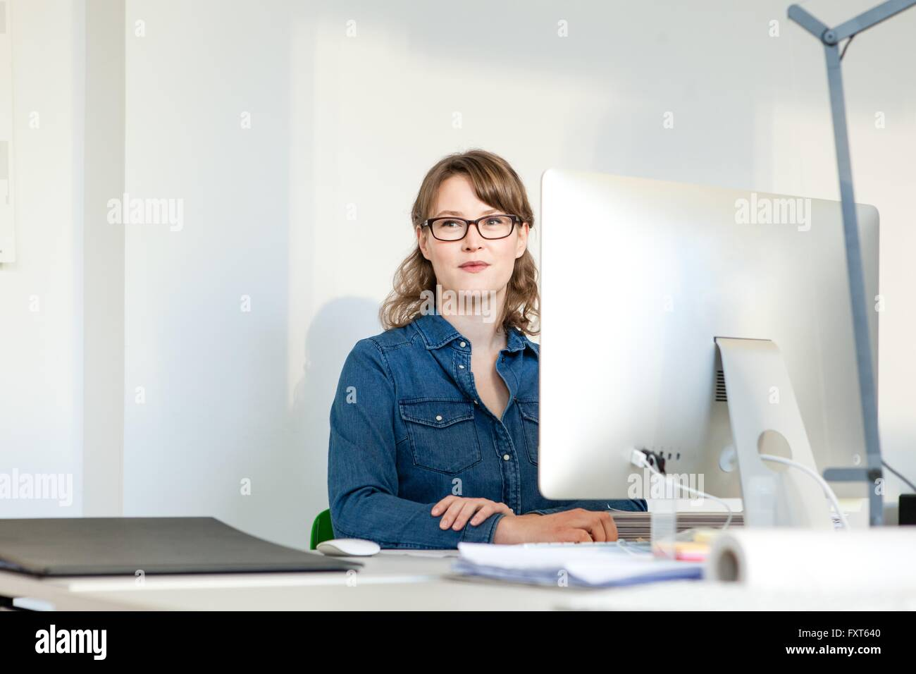 Young woman wearing eyeglasses sitting at desk using computer looking away smiling - Stock Image