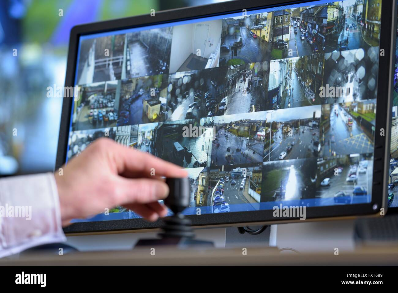 Close up of hand on camera control joystick in control room with video wall - Stock Image