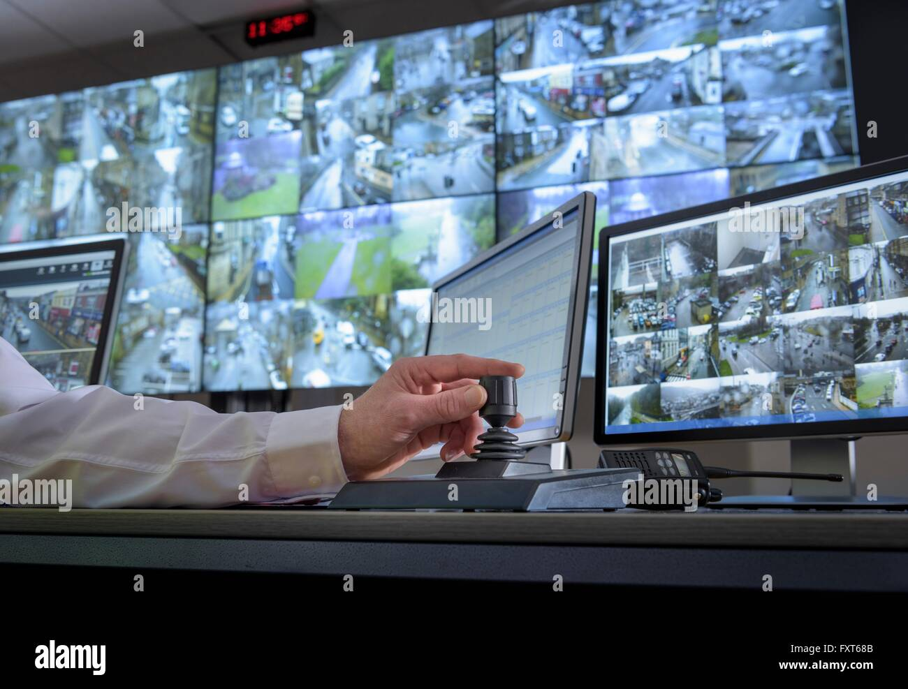 Detail of hand on camera control joystick in control room with video wall - Stock Image