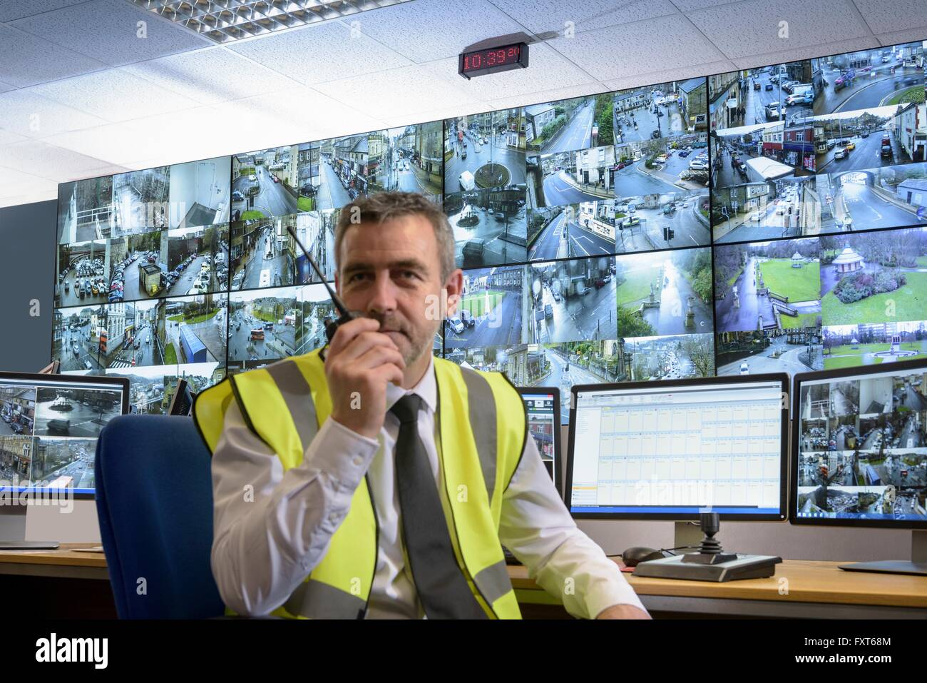 Portrait of security guard using walkie talkie in security control room with video wall - Stock Image
