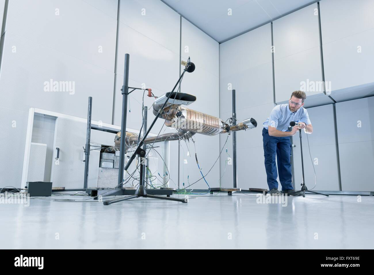 Engineer testing vehicle exhaust system in anechoic chamber - Stock Image