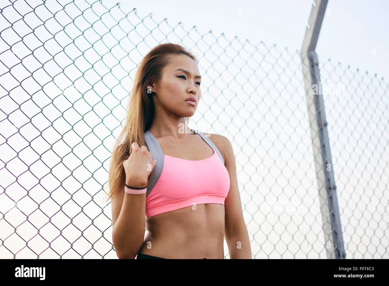Young woman wearing crop top by wire fence - Stock Image