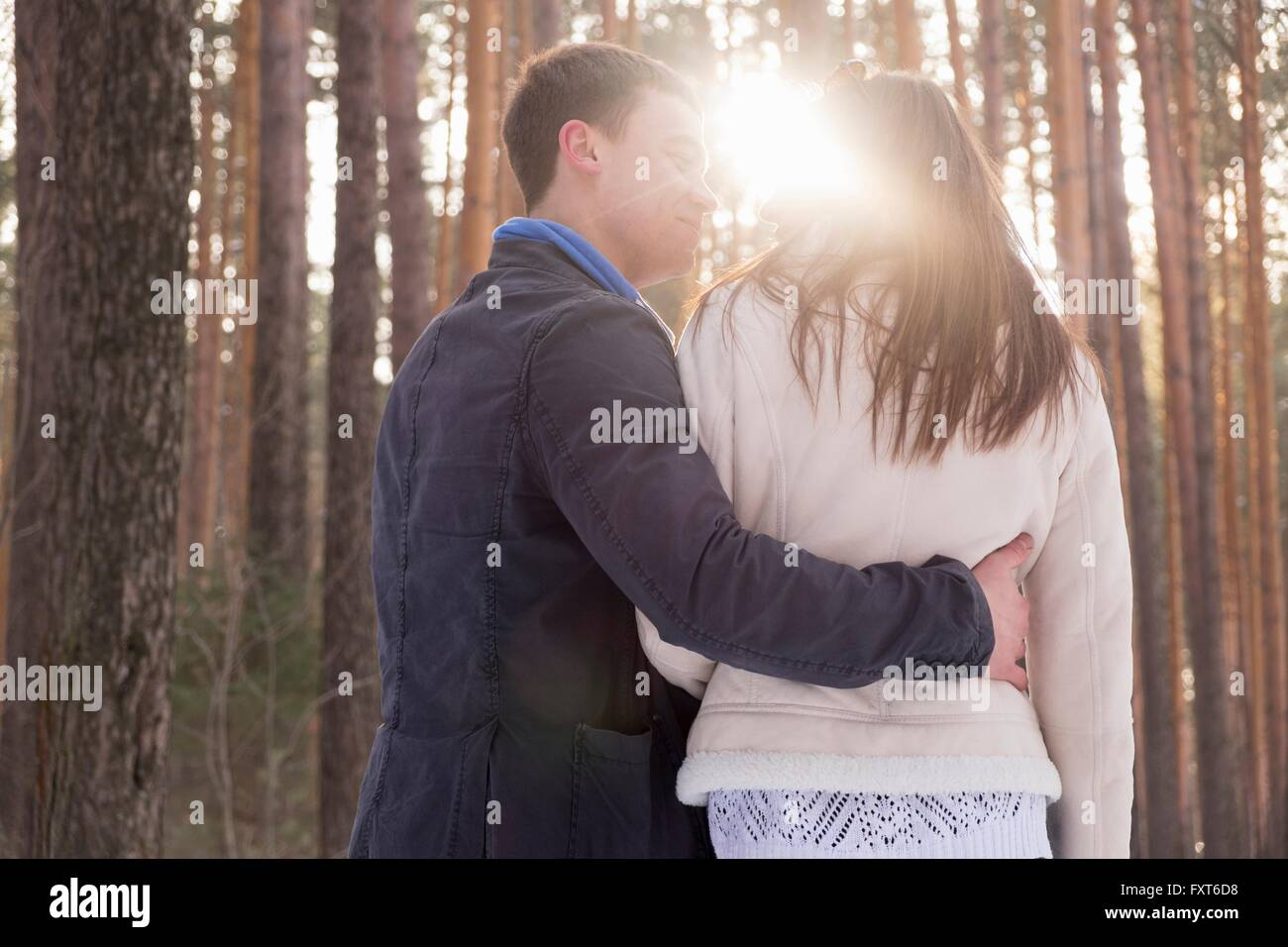 Young man guiding woman in forest - Stock Image