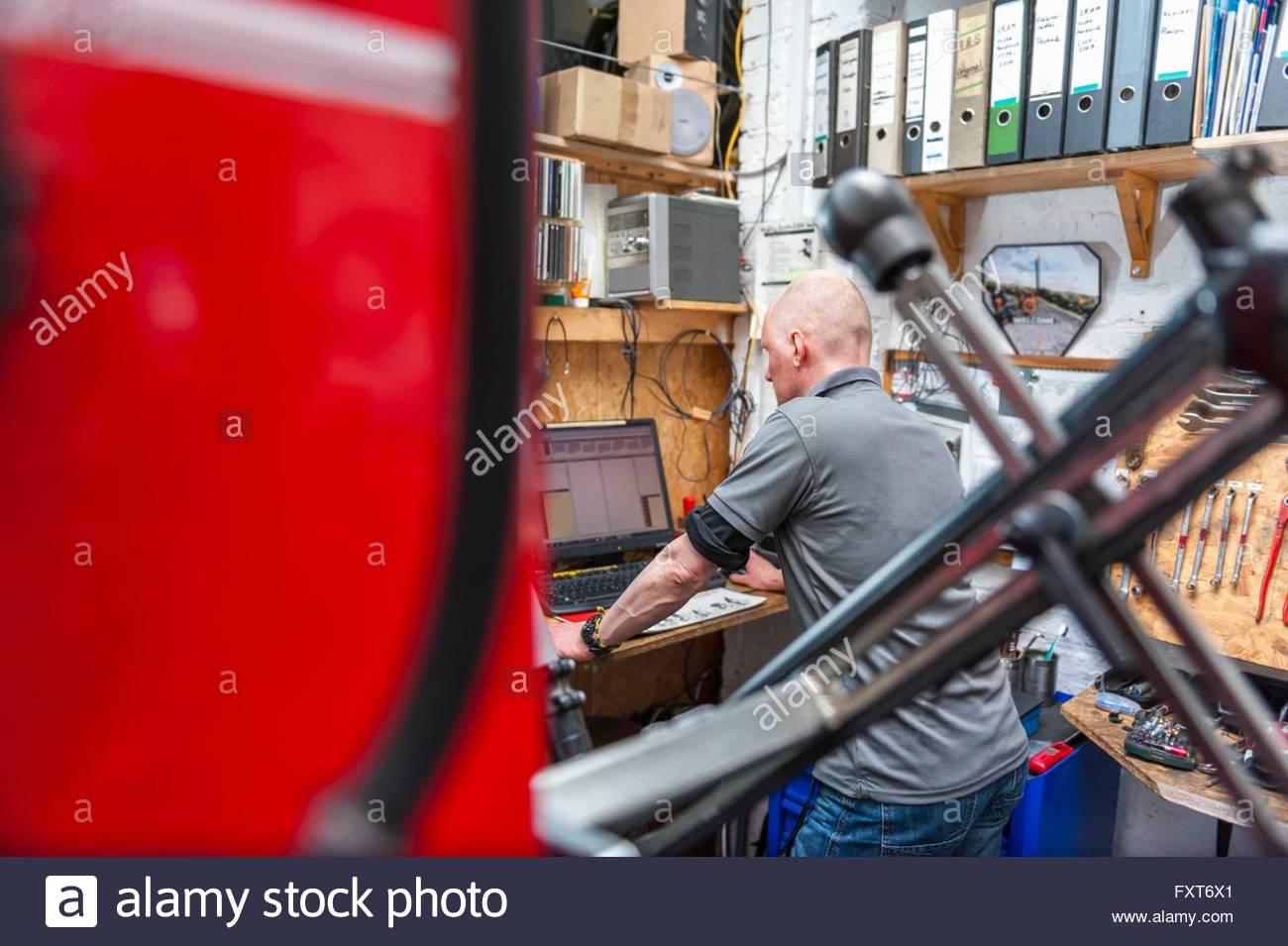 Mechanic using computer in workshop - Stock Image
