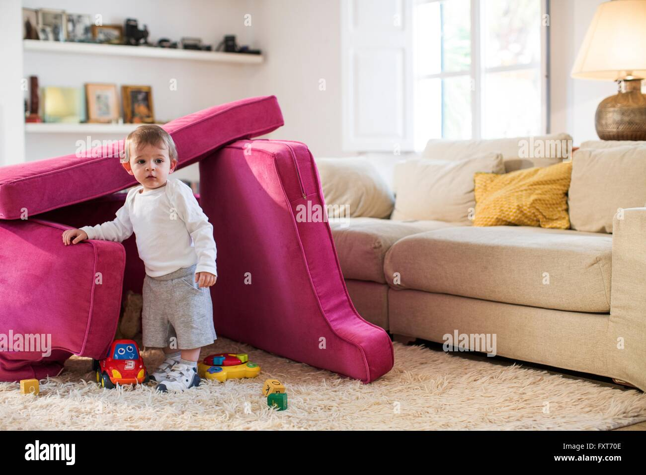 Baby boy playing in fort made from sofa cushions Stock Photo