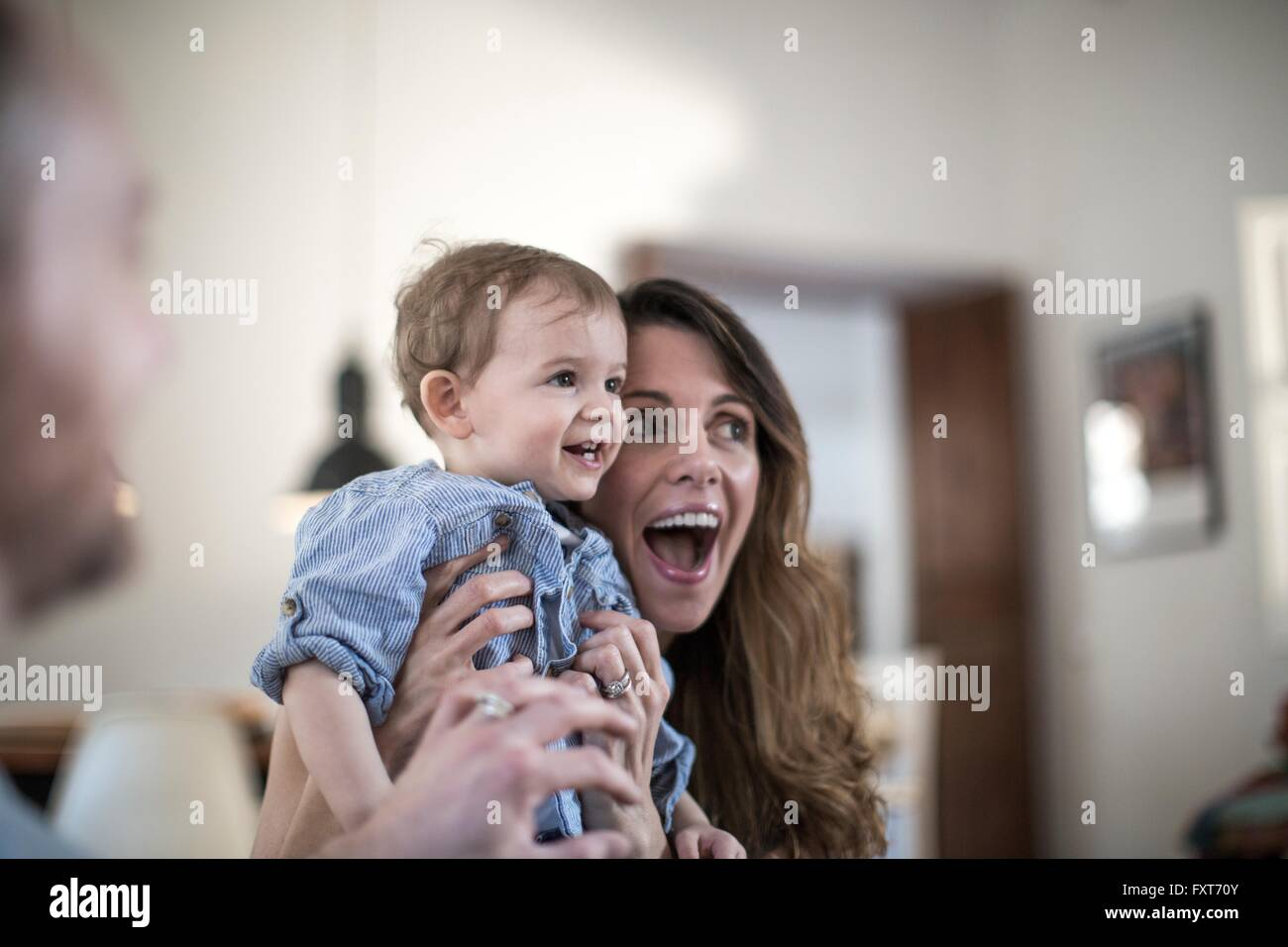 Mother holding smiling baby boy, open mouthed in surprise - Stock Image