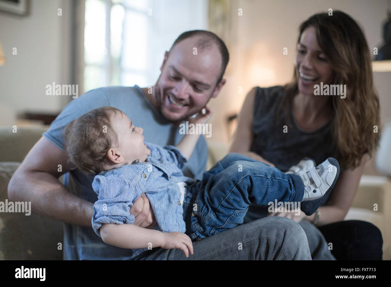 Parents sitting playing with smiling baby boy - Stock Image