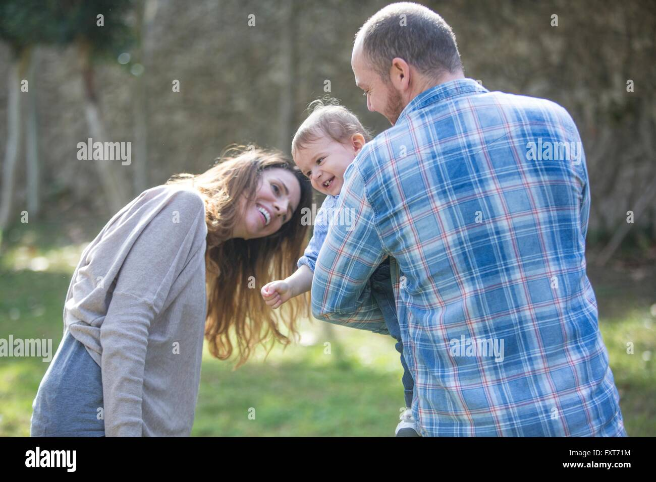 Parents holding smiling baby boy, playing - Stock Image