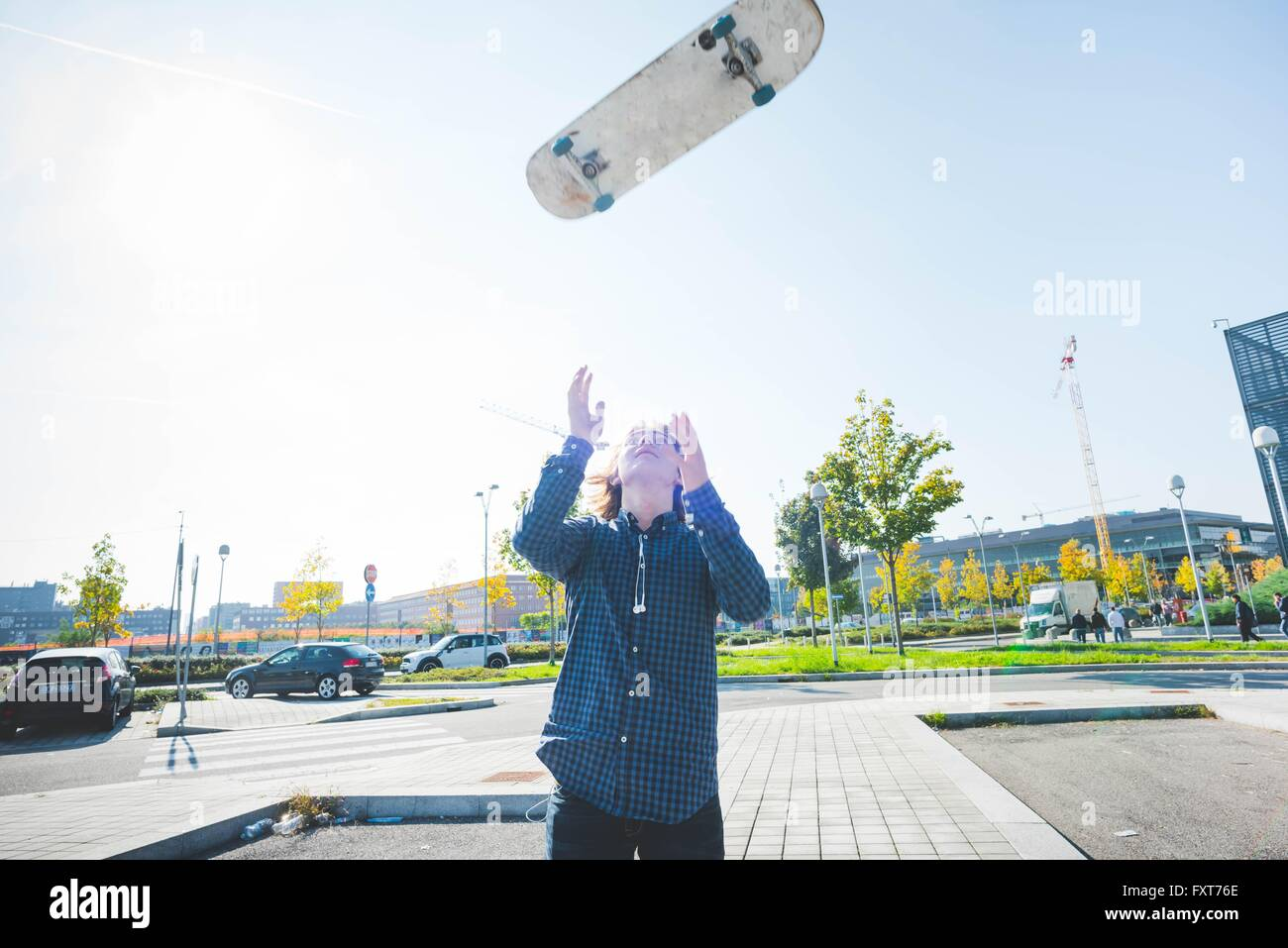 Young male urban skateboarder throwing skateboard mid air - Stock Image