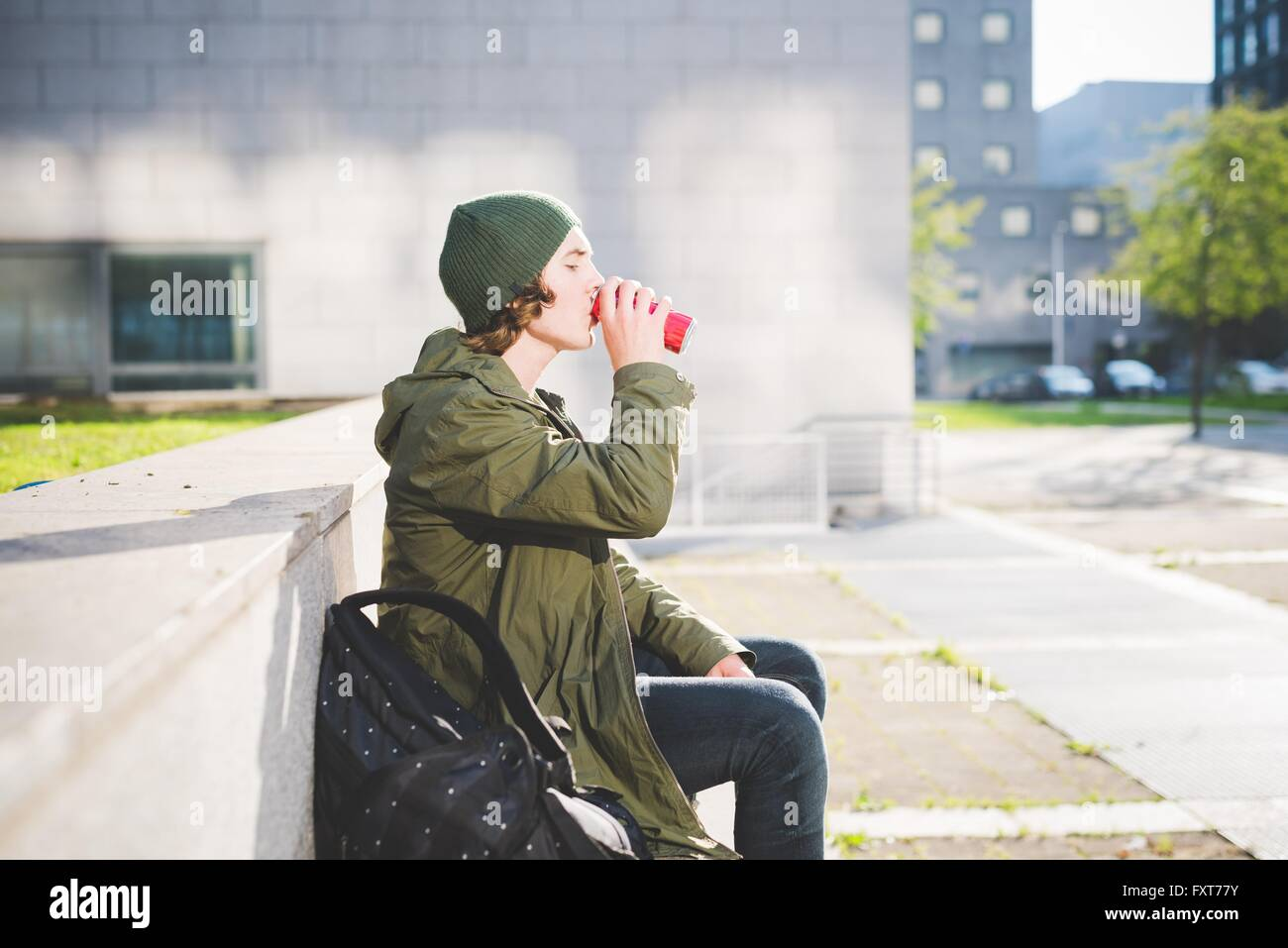 Young man sitting on urban wall drinking from can Stock Photo