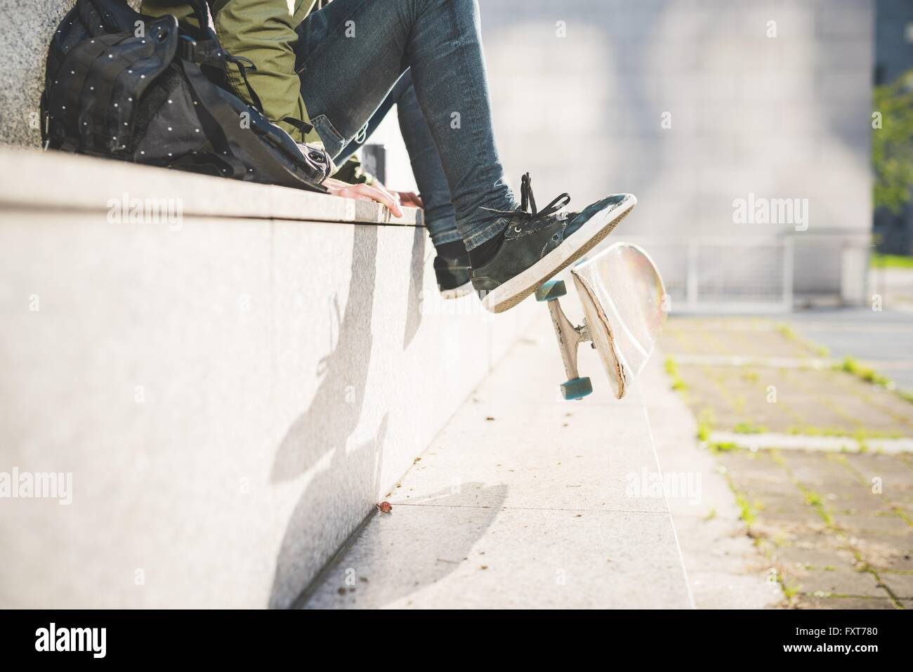 Waist down view of young male urban skate boarder sitting on wall flipping skateboard with feet - Stock Image