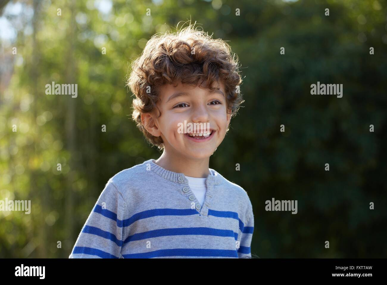 Portrait of curly haired boy looking away smiling - Stock Image
