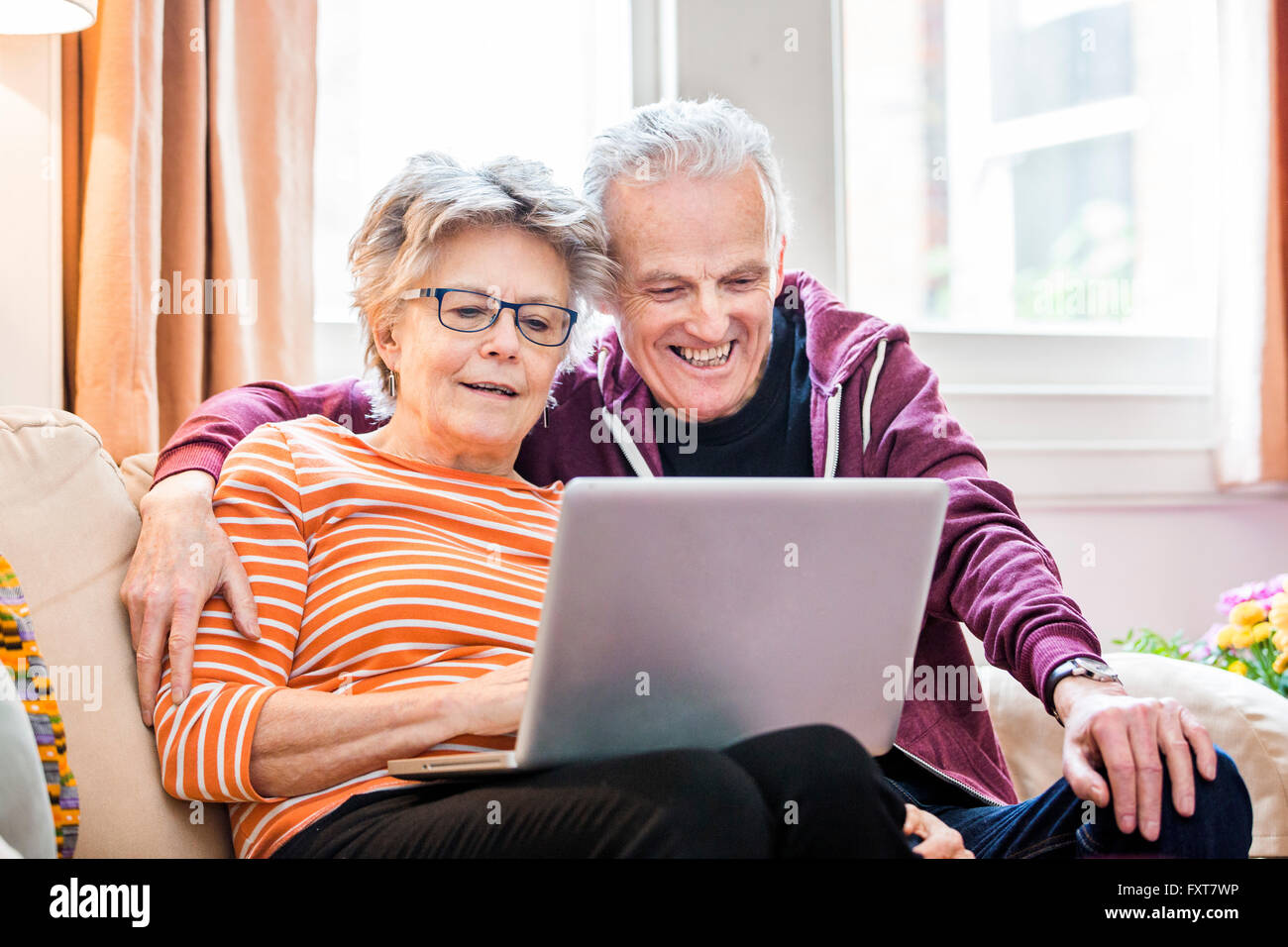 Senior couple on living room sofa looking at laptop - Stock Image
