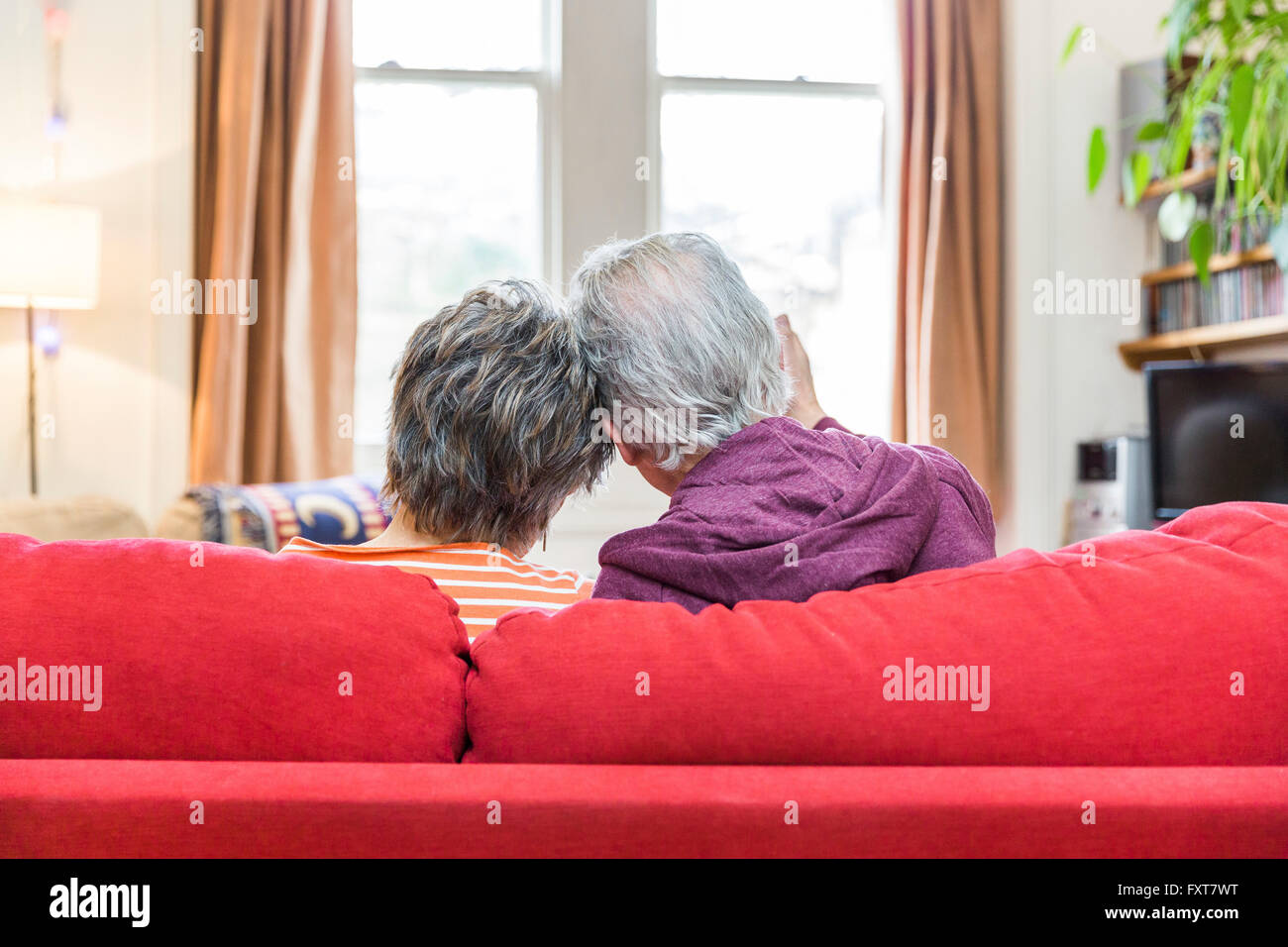 Rear view of romantic senior couple on living room sofa with heads together - Stock Image