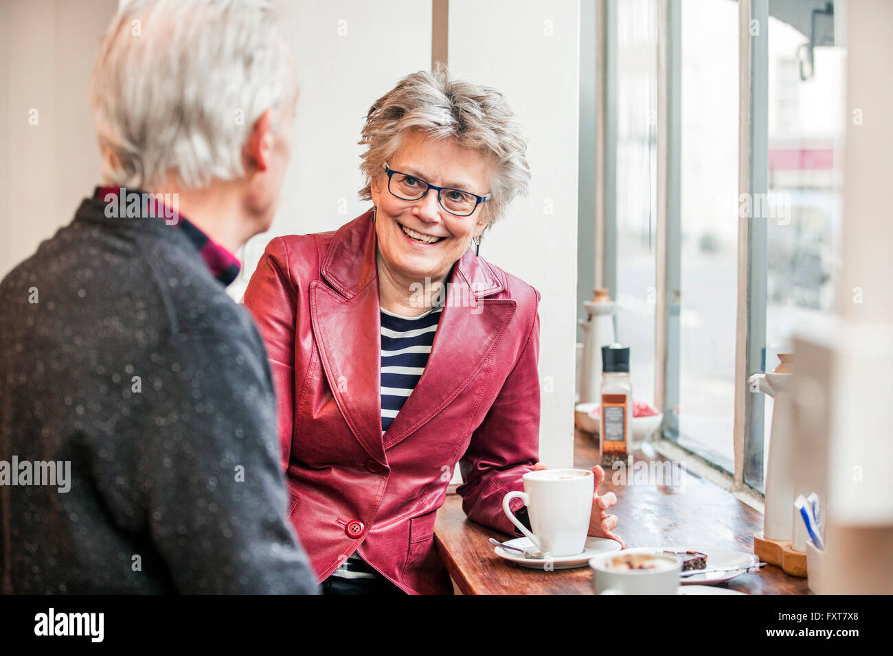 Senior couple chatting in cafe window seat - Stock Image