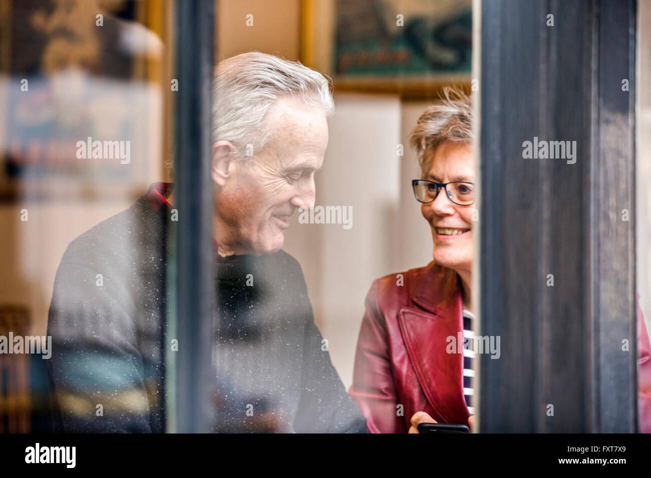 Senior couple sitting at cafe window seat chatting - Stock Image