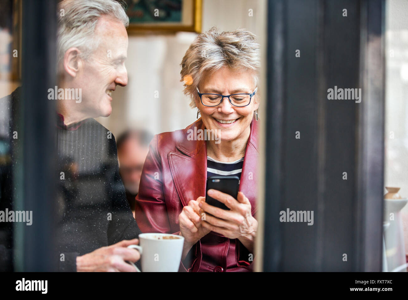 Senior couple sitting at cafe window seat drinking coffee and texting on smartphone - Stock Image