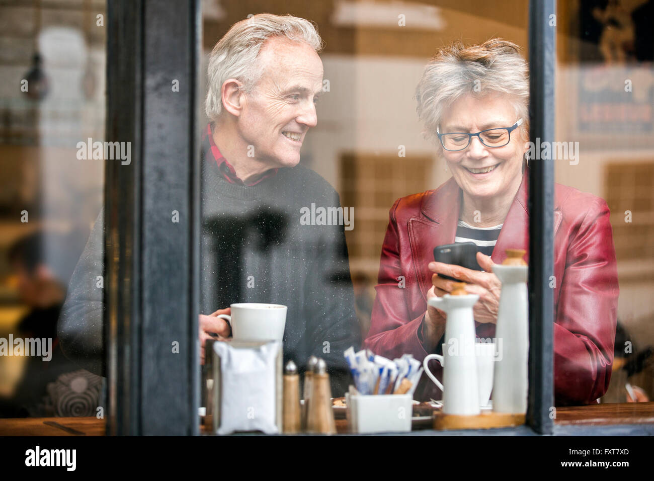 Senior couple in cafe window seat drinking coffee and texting on smartphone Stock Photo