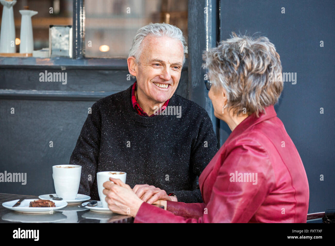 Senior couple at sidewalk cafe drinking coffee and chatting - Stock Image