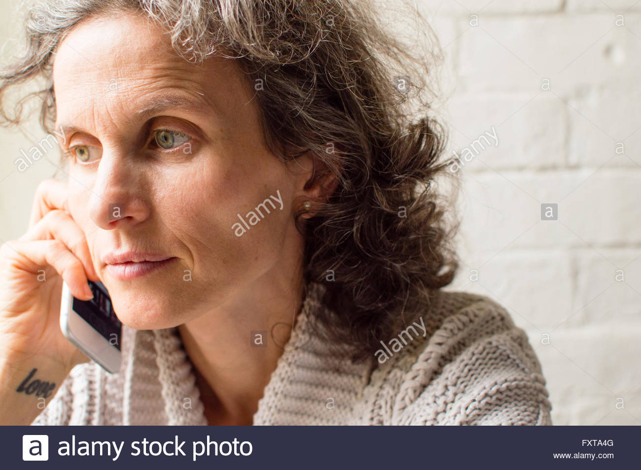 Middle aged woman, with grey hair looking thoughtful and using smart phone (selective focus) - Stock Image