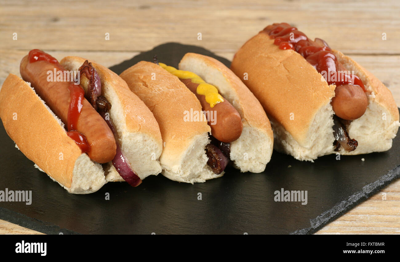 Three hot dogs on bread rolls with mustard and ketchup Stock Photo